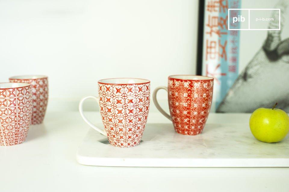 Ces mugs de faïence affichent des motifs géométriques et floraux d\'un rouge vif, délicatement peints sur fond blanc