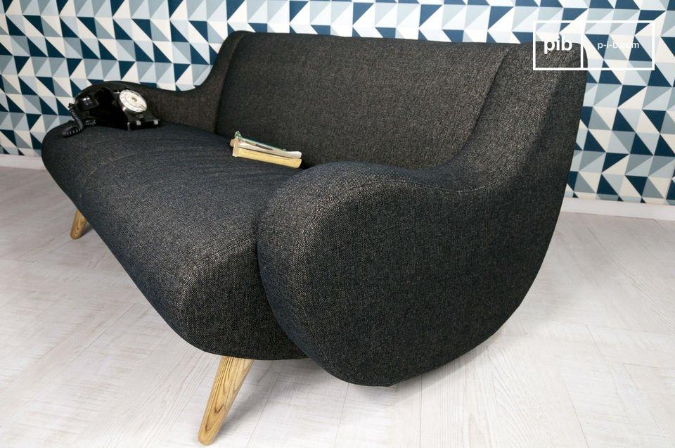 Bien installé sur ses pieds de chêne massif, et doté de larges accoudoirs tout arrondis, ce canapé design revendique ses origines dans des pièces de design des années 50