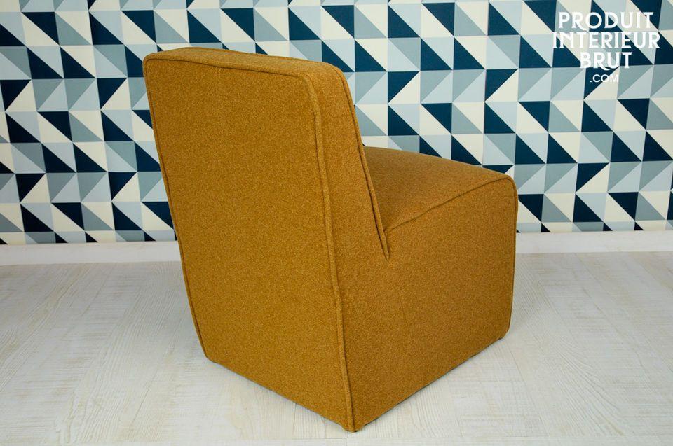 La couleur ocre de la feutrine dont ce fauteuil est couvert participe à son look fifties