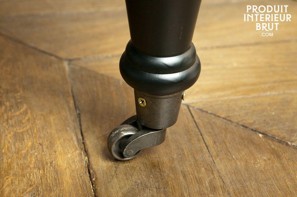 Les pieds en bois noir se prolongent à l\'avant par des roulettes en laiton