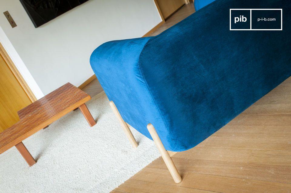Les formes généreuses du fauteuil Viela s\'accompagnent d\'un revêtement en velours bleu profond