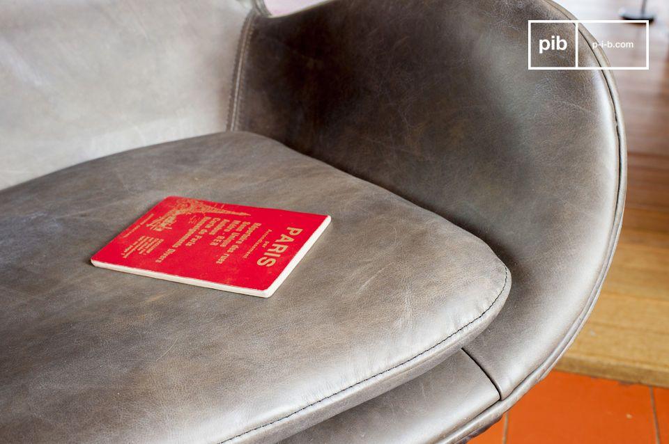 La base en étoile de ce fauteuil retro est en métal poli, elle permet la rotation du siège