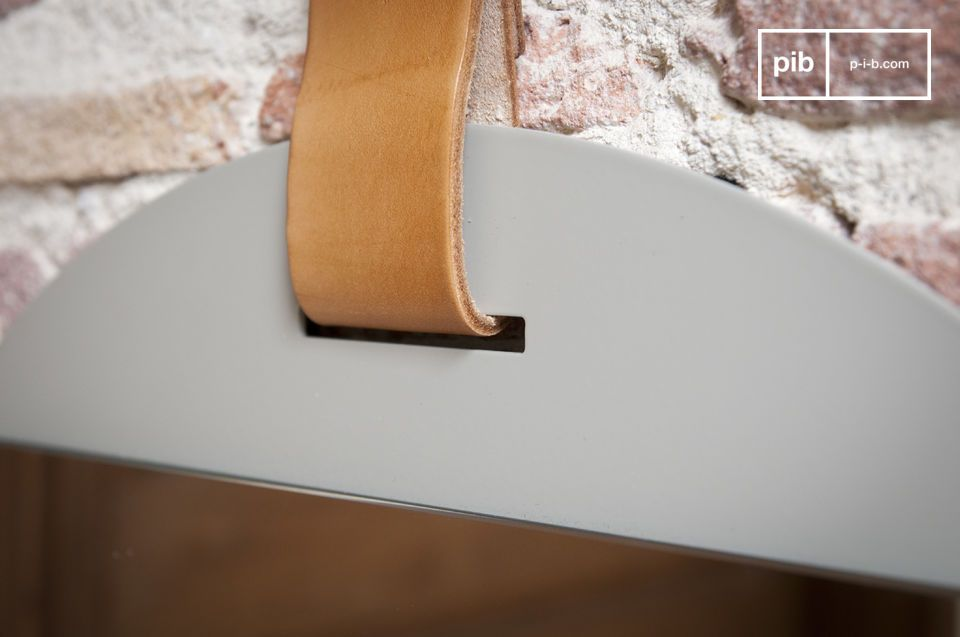 Suspendu par une épaisse lanière de cuir, ce grand miroir d\'entrée affiche un style très sobre