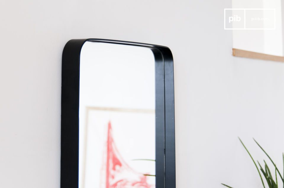 Un grand miroir à cadre noir, au style discret mais affirmé