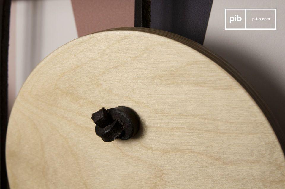 Les disques de bois verni sont suspendus par des lanières de cuir