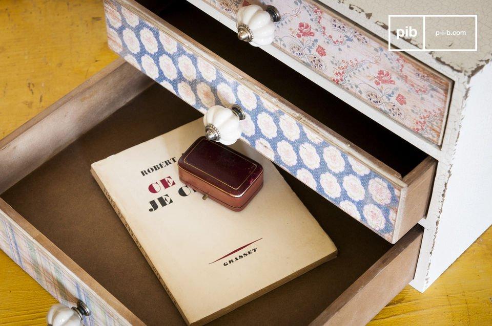 Ce petit meuble rassemble trois tiroirs recouverts de papiers peints d\'inspiration florale qui