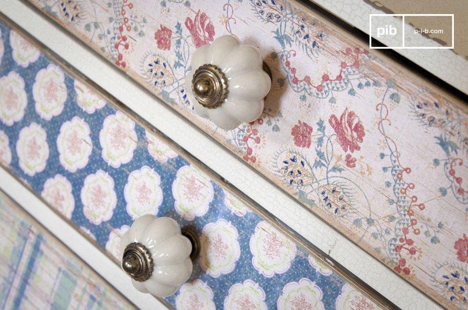 Sur chacun des tiroirs une poignée en porcelaine blanche garnie d\'un bouton en laiton vient
