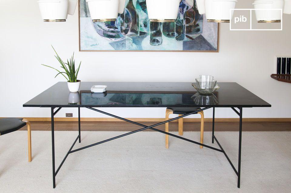 Un piétement minimaliste en aluminium noir mat soutient le plateau