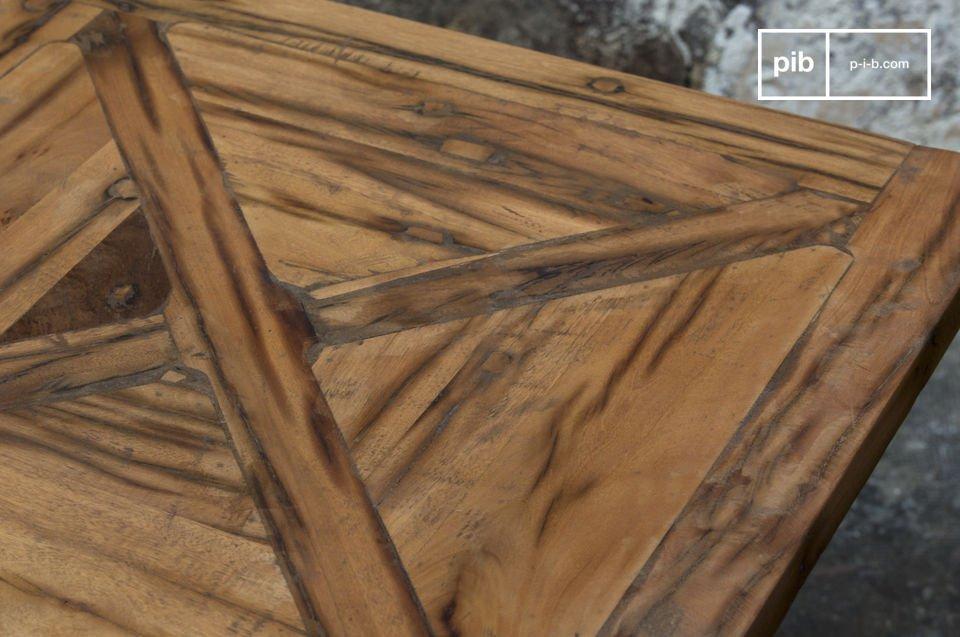 Son plateau en bois recyclé laisse apparaître des traces des anciens usages des planches qui le composent, qui font de chaque table une pièce unique